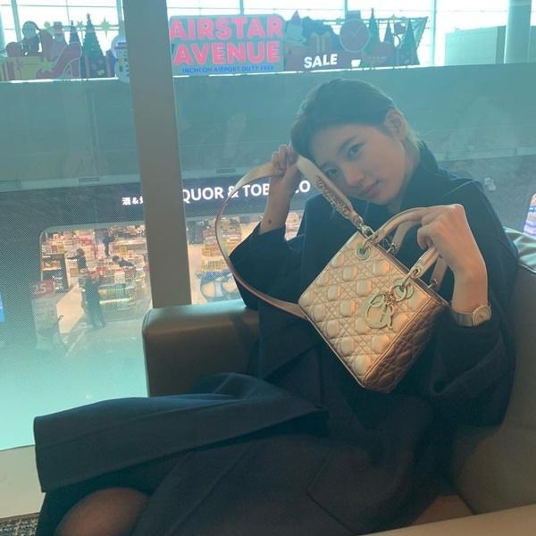 Suzy tạo dáng khoe túi xách hàng hiệu ở sân bay.