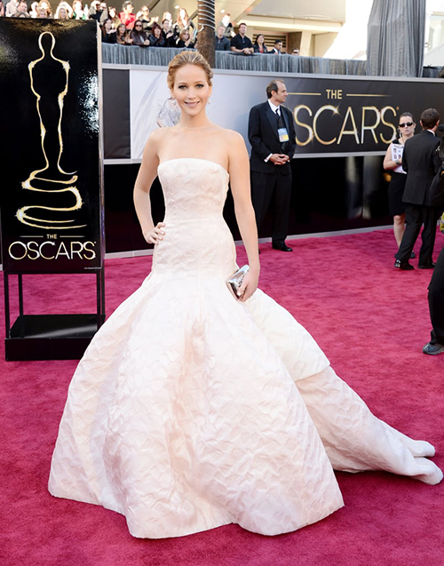 Bộ đầm dạ hội cầu kỳ của Dior Haute Couture giúp Jennifer Lawrence xinh đẹp trên thảm đỏ, tuy nhiên sau đó lại khiến cô gặp phải cú vồ ếch đi vào lịch sử khi đang lên sân khấu nhận giải. Thiết kế bồng bềnh là một thách thức đối với những cô nàng không quen mặc đồ vướng víu, đi giày cao gót như Jennifer.