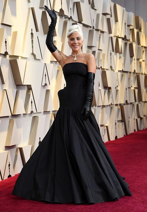 Trên thảm đỏ lễ trao giải Oscar 2019, Lady Gaga thành tâm điểm khi tái hiện diện mạo sang trọng của huyền thoại Audrey Hepburn. Ngôi sao A Star Is Born diện đầm quây đen của Alexander McQueen, kết hợp găng tay tông xuyệt tông.
