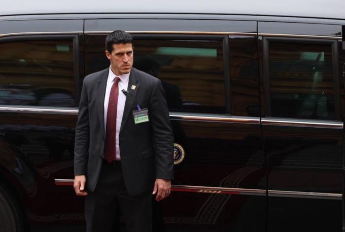 <p> Ánh mắt hình viên đạn của một mật vụ khi đứng gác bên chiếc xe của Tổng thống. Ảnh: <em>Ngọc Thành.</em></p>