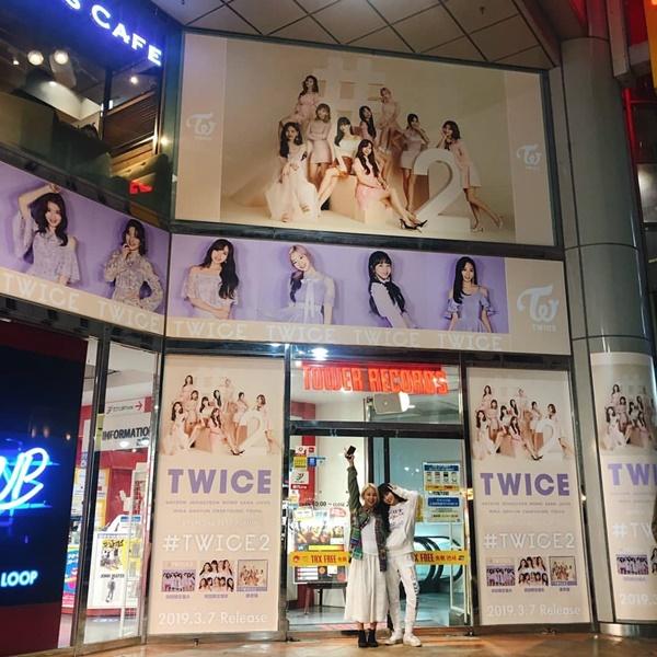 Hai thành viên Twice tự hào đứng pose hình cùng poster nhóm ở trung tâm thương mại.
