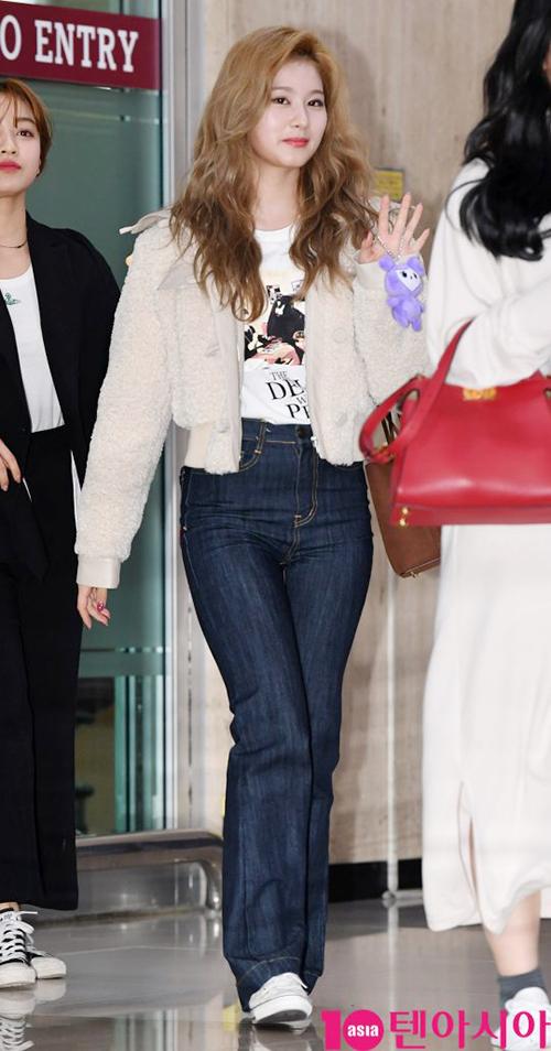 Kiểu quần cạp cao khiến đôi chân của Sana bỗng dài bất ngờ. Nữ ca sĩ chọn trang phục sân bay theo phong cách những năm 80 với quần ống loe, mái tóc xoăn.
