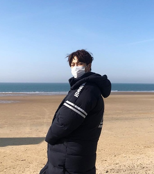 L (Infinite) phải mặc áo to sụ khi đi ngắm biển lúc tiết trời còn lạnh. Anh chàng được fan khen đeo khẩu trang cũng không che được vẻ mỹ nam.