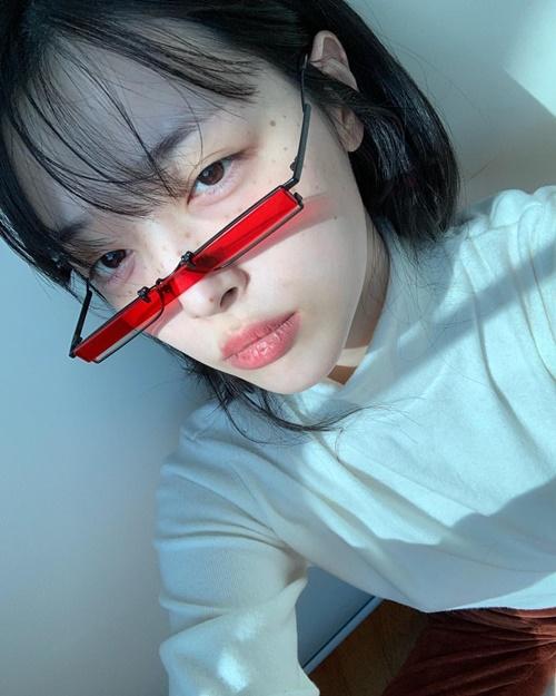 Sulli trang điểm mặt tàn nhang, để môi khô khốc như sắp bong cả da. Cô nàng làm mặt ngầu với chiếc kính tí hon.