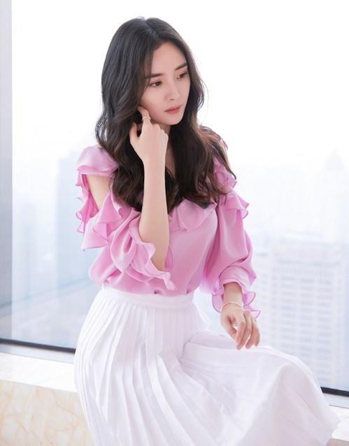 Dương Mịch đẹp nền nã với chiếc áo bèo nhún màu hồng điệu đà, phối chân váy xếp ly. Hồng là sắc màu được nhiều sao nữ ưa chuộng trong thời điểm hoa anh đào nở.