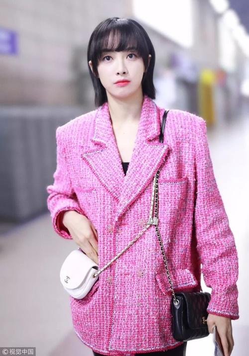 Tống Thiến (Victoria) mặc áo khoác vải tweed màu hồng rực mà không sợ sến, giúp cô có ngoại hình nổi bật hơn khi ra sân bay.