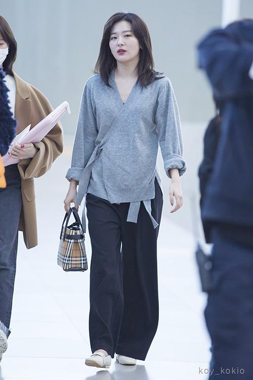 Seul Gi chọn những item có tông màu trầm, phom dáng rộng rãi để tiện di chuyển. Nữ ca sĩ sử dụng túi xách của Burberry để khẳng định đẳng cấp.