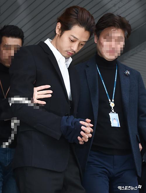 Jung Joon Young mặc vest đen và áo somi trắng. Y bị trói chặt bằng dây thừng, còng tay trong quá trình áp giải.