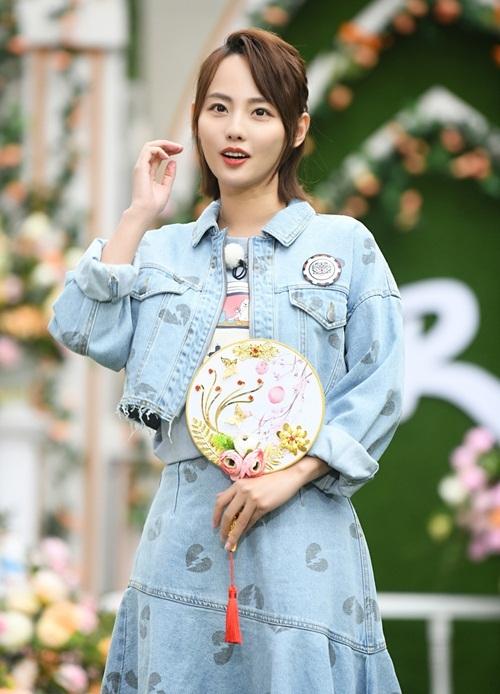 Trương Gia Nghê mặc cả cây denim tông xuyệt tông với áo khoác tua rua và chân váy in họa tiết.