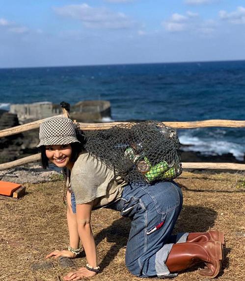 Miu Lê chọn quần yếm hàng hiệu kết hợp mũ bucket đáng yêu khi dọn vỏ lon ven biển.