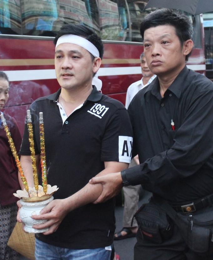 <p> Em trai nam nghệ sĩ cầm bát hương bước đi thất thểu, phải có người dìu khi đoàn xe tang di chuyển từ chùa Ấn Quang về nghĩa trang để mai táng.</p>