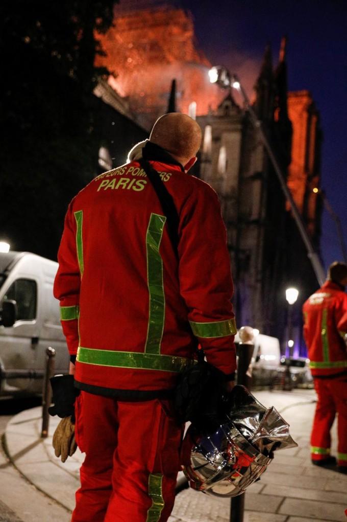 <p> Bóng lưng đau đáu của một người lính cứu hỏa đứng nhìn các đồng đội đang nỗ lực dập lửa.</p>