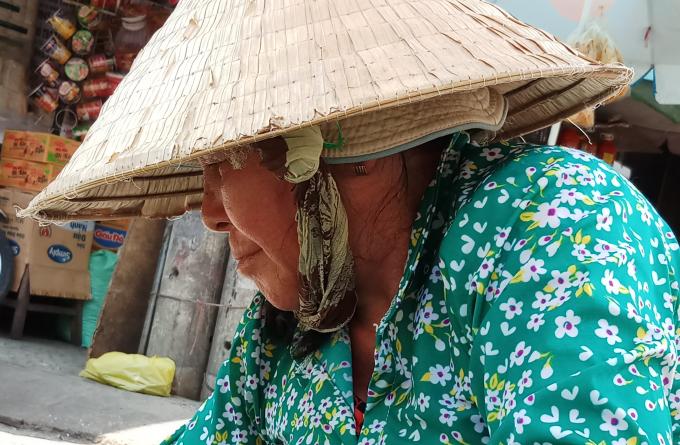 <p> Một tiểu thương tại chợ Phú Lâm, quận Bình Tân đội nhiều loại mũ, mặc áo lớp trong lớp ngoài để tránh nắng.</p>