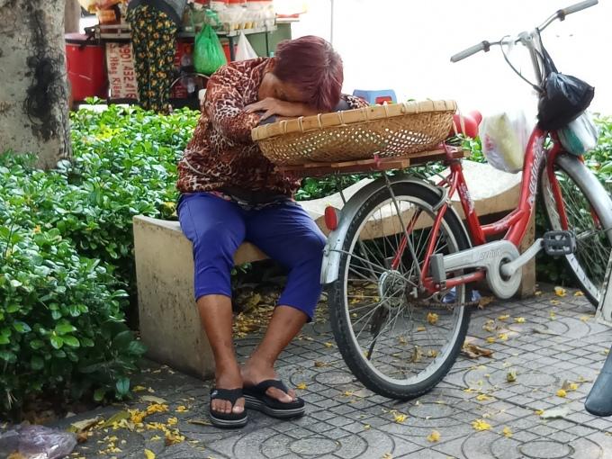 <p> Giữa trưa nắng gắt, một người bán hàng rong tìm nơi có nhiều bóng mát để tránh nắng và tranh thủ chợp mắt.</p>