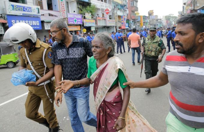 <p> Một phụ nữ Sri Lanka lớn tuổi được giúp đỡ gần đền St Anthony sau vụ nổ ở Colombo. <em>Ảnh: Eranga Jayawardena / AP</em></p>