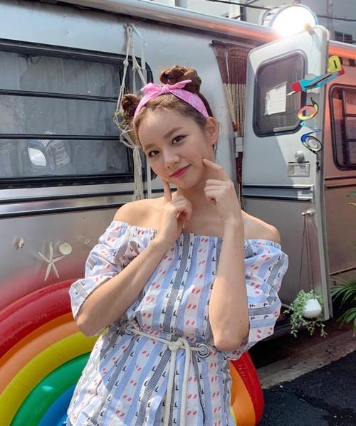 Hye Ri khoe style đậm chất hè với áo trễ vai, kiểu tóc búi Pucca buộc nơ hồng xì tin.