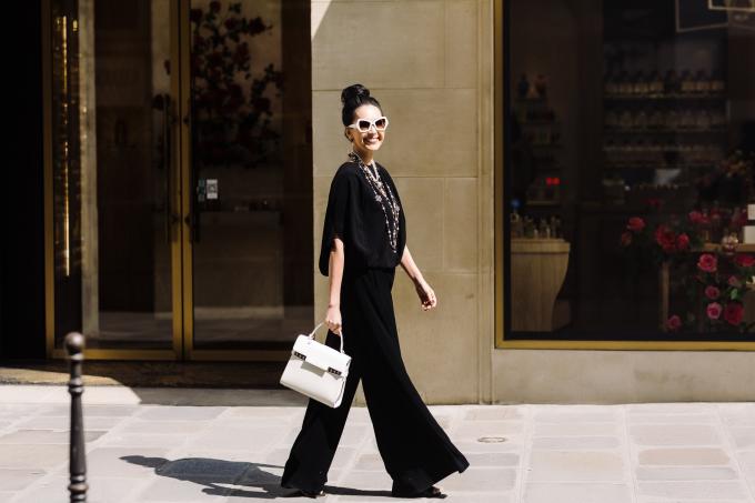 <p> Quần ống loe rộng phối áo cùng sắc đen được Diễm My nhấn nhá bằng chuỗi vòng cổ ngọc trai của Chanel và túi Delvaux, mắt kính to bản của Celine.</p>