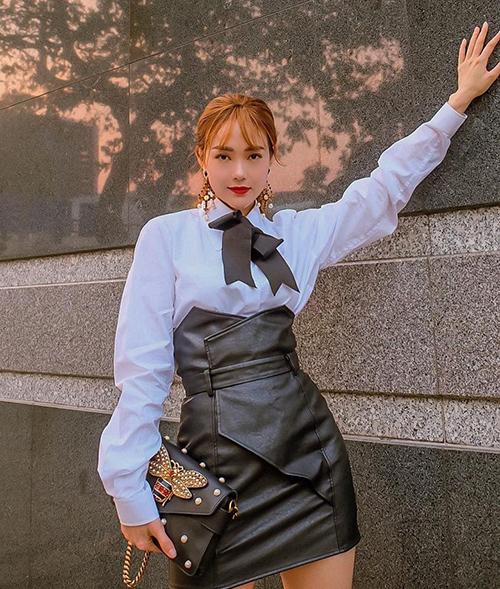 Minh Hằng mix sơ mi trắng tay bồng cùng chân váy da, kết hợp phụ kiện lấp lánh tăng độ sành điệu.