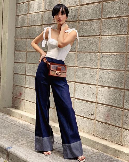 Áo hai dây và quần ống loe giúp Khánh Linh tăng thêm độ cao ráo. Cô nàng khoe chiếc túi đeo thắt lưng là sản phẩm mới nhất của Louis Vuitton.