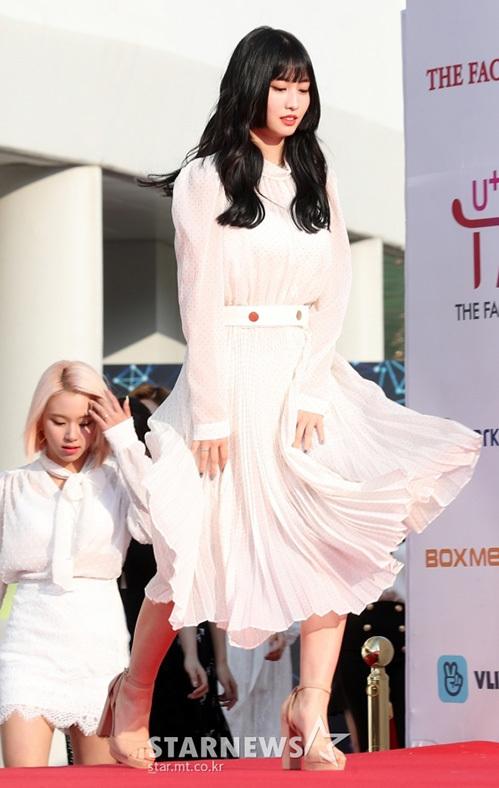 Momo vội vàng giữ váy khi cơn gió to thổi qua.