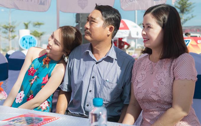 <p> Cả gia đình chăm chú theo dõi sự kiện. Thi thoảng, Tường Linh quay sang chỉnh trang lại áo cho bố, quạt cho mẹ dưới tiết trời nóng nực.</p>