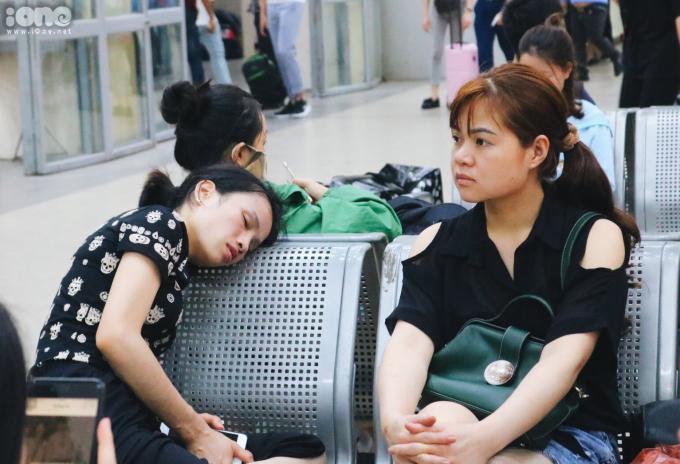 <p> Một người phụ nữ đã quá mệt, ngả lưng trên ghế đợi chuyến xe của mình.</p>