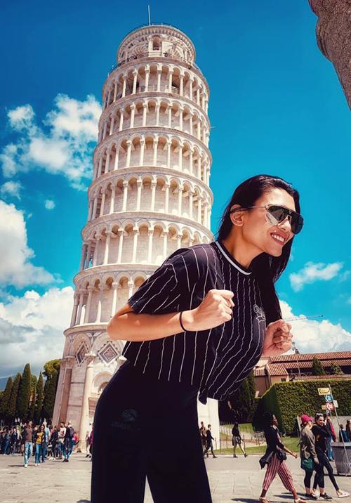 Võ Hoàng Yến nghịch ngợm tạo dáng như đang gồng gánh cả tháp nghiêng Pisa trên lưng.