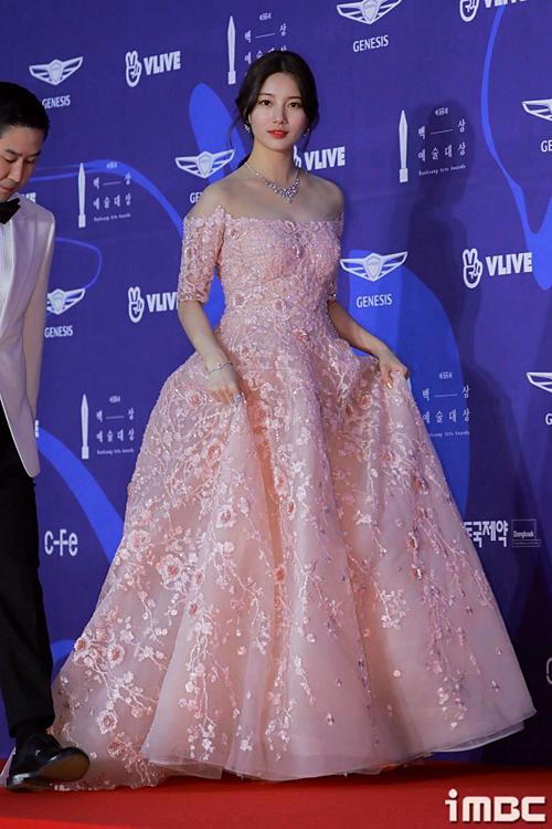 Tham dự sự kiện, Suzy lựa chọn đầm xòe hở vai màu hồng nữ tính với điểm nhấn là những chi tiết đính hoa ren tinh tế. Đây là thiết kế của thương hiệu Marie Belle.