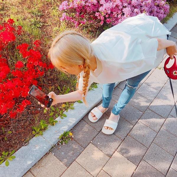 Tae Yeon tết tóc xì tin, vừa dắt cún đi dạo công viên vừa tranh thủ chụp ảnh hoa hoét.