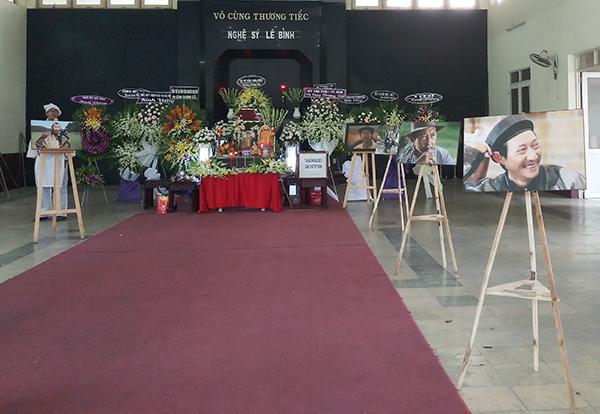 Hình ảnh của Lê Bình trong các bộ phim được in và xếp thành hàng quanh quan tài ở nhà tang lễ.