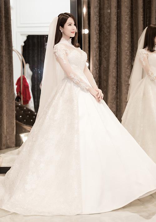 Đi cùng chiếc váy chất liệu gấm họa tiết sang trọng là khăn voan dài nhưng cũng có kiểu cách đơn giản để trông không bị rối mắt. Đuôi váy không quá dài để thuận tiện cho việc đứng chào đón từng khách mời. Phía Diệp Lâm Anh tiết lộ, giá của bộ trang phục này là 120 triệu đồng.