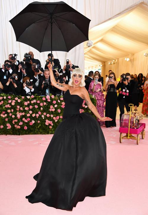 Sau đó, cô được trợ lý kéo lớp choàng hồng dài phía ngoài ra, để lộ bên trong là bộ váy quây đen gợi cảm.