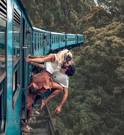 Camille và Jean đu người ra khỏi tàu hỏa để chụp ảnh.