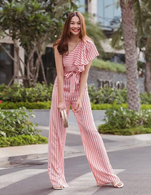 Bộ jumpsuit kẻ sọc lệch vai mang đến cho Thanh Hằng vẻ ngoài tươi trẻ, đồng thời thân hình càng thêm cao ráo.
