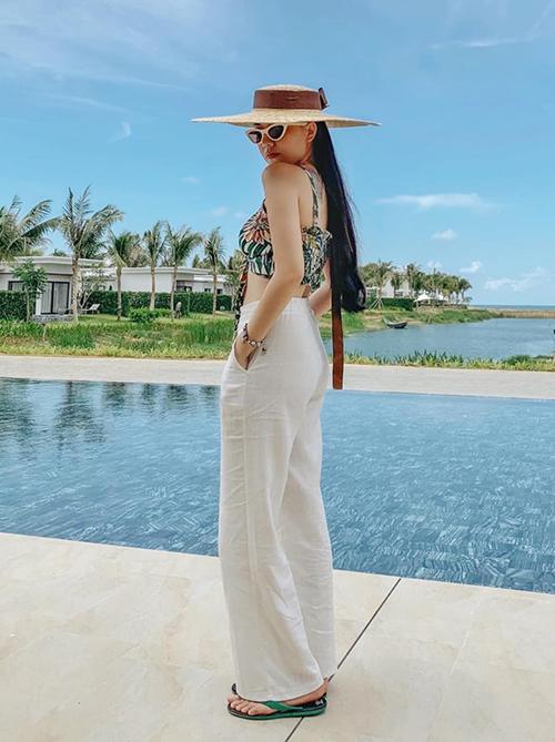 Set đồ croptop đi cùng quần linen ống rộng, mũ cói vành to là lựa chọn đầy lý tưởng của Băng Di khi đi biển.