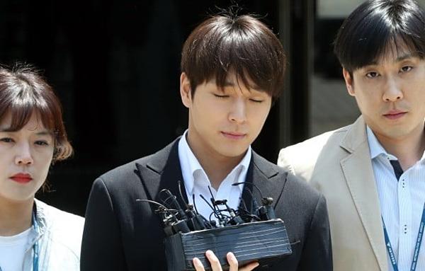 Choi Jong Hoon bị phóng viên bao vây khi bị áp giải lên xe cảnh sát.