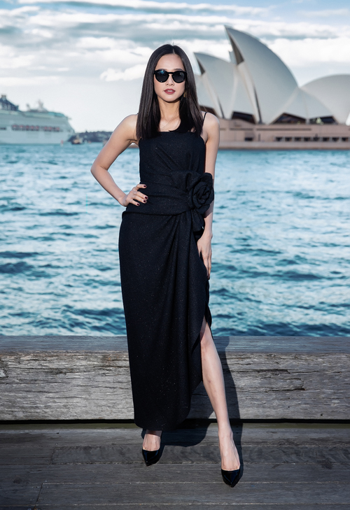 Hoa hậu Phụ nữ Việt Nam qua ảnh 2006 Dương Mỹ Linh diện thiết kế bất đối xứng với với điểm nhấn là những đường gấp và hoạ tiết hoa 3D to ở thắt eo. Giày, mắt kính và hoa tai được người đẹp chọn đi kèm trang phục có thiết kế tối giản.