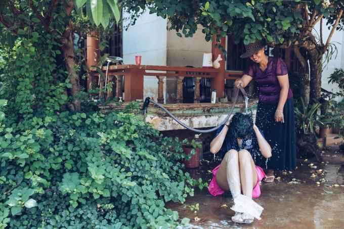 <p> H'Hen Niê trở lại thời thơ ấu khi được mẹ tắm gội cho bên góc sân nhà.</p>