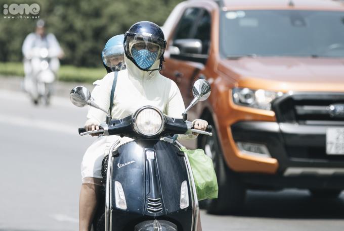 <p> Người dân khi đi xe máy phải trang bị áo chống nắng, bịt khẩu trang kín mít.</p>