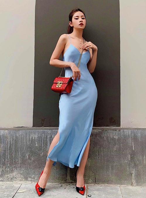 Chiếc váy hai dây lụa mềm kiểu dáng như đồ ngủ được Chi Pu biến thành đồ sang chảnh dạo phố bằng cách mix cùng túi, giày hàng hiệu tông đỏ.