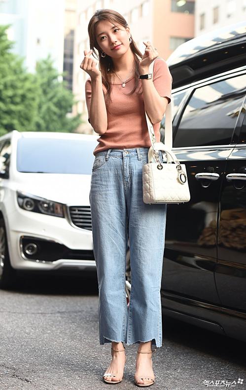 Người đẹp sinh năm 1994 mặc trang phục giản dị, tạo dáng vẫy chào fan và báo chí.