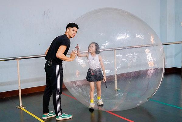 Khánh An đưa ra bài học catwalk với lụa và trái bóng khổng lồ. Cô bé 7 tuổi nhiệt tình hướng dẫn cậu học trò lớn nghịch ngợm những kỹ năng trình diễn thời trang. Không ít tình huống và sự cố xảy ra bởi sự nghịch ngợm của cả hai.