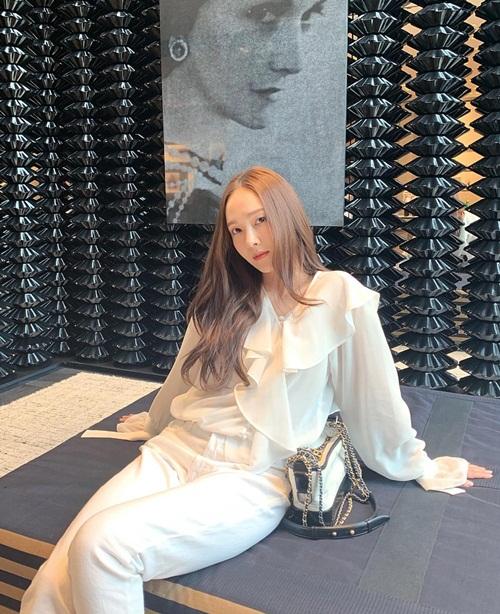 Jessica diện cây trắng với áo cổ bèo tay loe điệu đà.