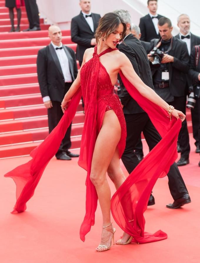 """<p> Bộ đầm đỏ xẻ tứ tung củaJulien Macdonald rất dễ bị """"sến"""", chỉ có những chân dài với làn da rám nắng, vóc dáng săn chắc và thần thái đỉnh cao như Alessandra Ambrosio mới có thể chinh phục.</p>"""
