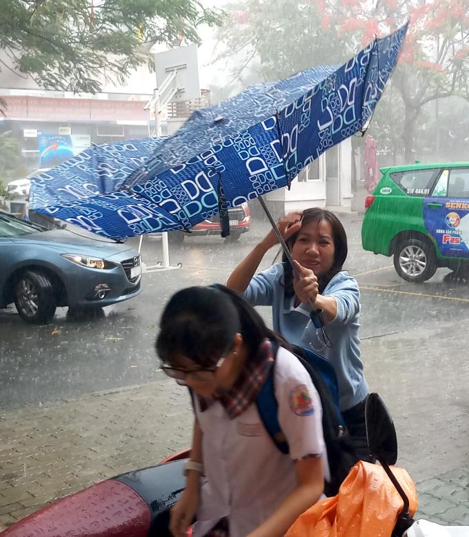 <p> Mưa kèm theo gió khiến những chiếc dù bị lật. Vị phụ huynh này khá vất vả khi che chở cho con gái bước từ cổng trường vào địa điểm thi để không bị ướt.</p>