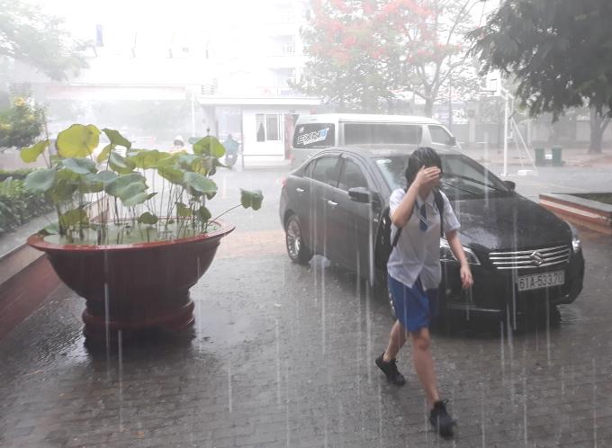 <p> Cô bé đầu trần và ướt sũng sau khi lội mưa từ cổng trường vào phòng thi.</p>