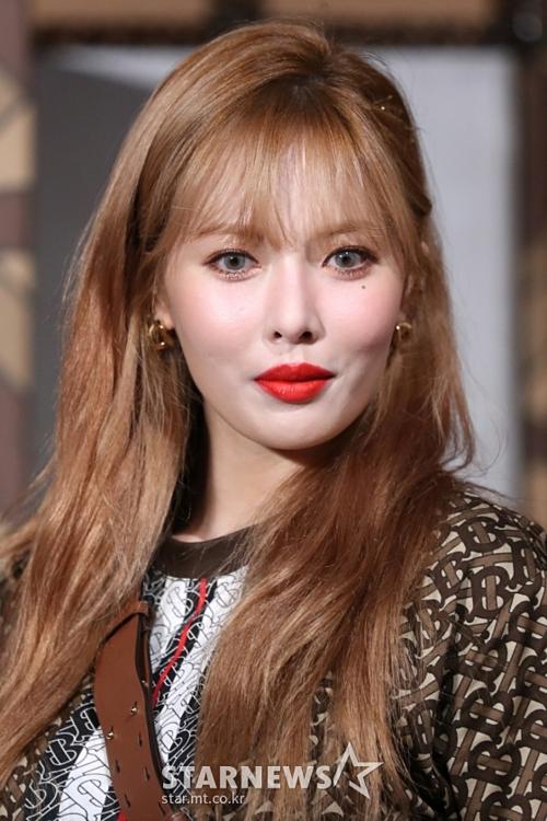 Hyuna đeo lenssáng màu, đôi môi tô son đỏ rực rỡ. Phong cách trang điểm của nữ ca sĩ nhận nhiều lời chê từ netizen Hàn. Trên Nate, nhiều người cho rằng Hyuna trông kém sắc như một bà cô kỳ quặc.