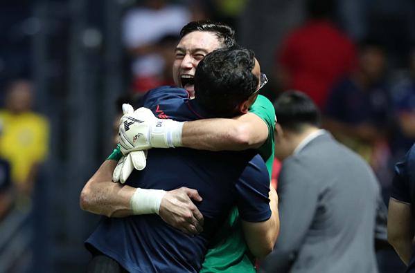 Văn Lâm ôm thành viên BHL ăn mừng chiến thắng.