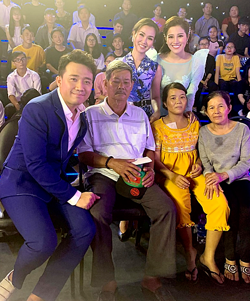 Trấn Thành và các nghệ sĩ chụp hình cùng gia đình chị Nguyễn Thị Hiền (áo vàng).