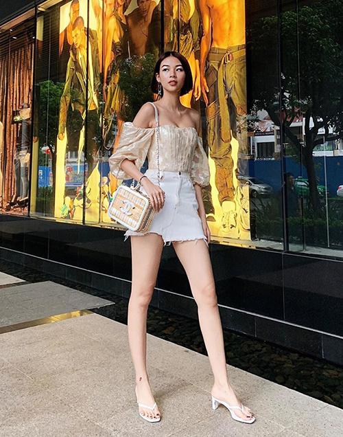 Phí Phương Anh diện áo trễ nải khoe vòng một gợi cảm. Cô nàng khéo mix cùng chiếc túi Chanel đậm chất hè.